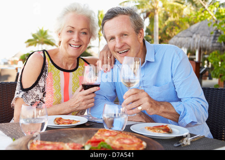Senior Couple Enjoying Meal In Outdoor Restaurant - Stock Photo
