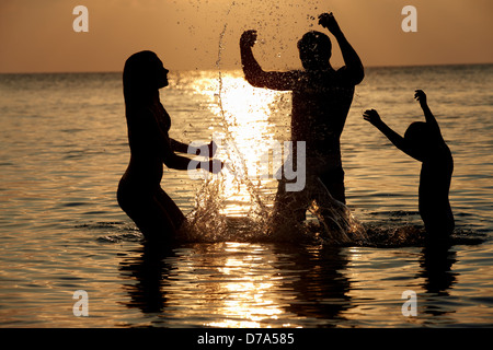Silhouette Of Family Having Fun In Sea On Beach Holiday - Stock Photo