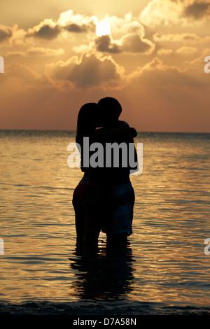 Silhouette Of Romantic Couple Standing In Sea - Stock Photo