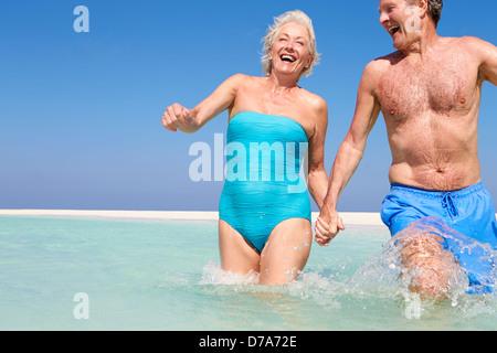 Senior Couple Having Fun In Sea On Beach Holiday - Stock Photo