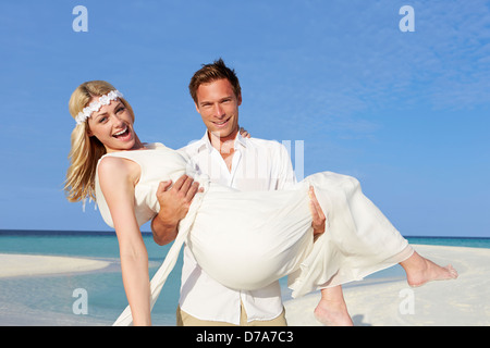 Groom Carrying Bride At Beautiful Beach Wedding - Stock Photo