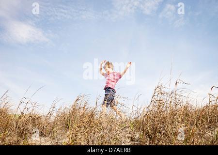 child running through dunes - Stock Photo