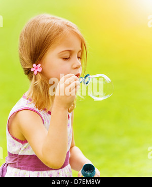 Closeup portrait of cute baby girl blowing soap bubbles in spring park, having fun outdoors, happy childhood concept - Stock Photo