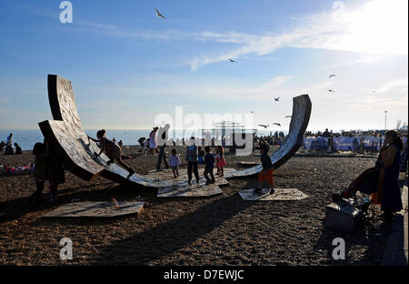 Brighton UK 6th May 2013 - Catching the last of the sun by the passacaglia sculpture on Brighton beach during the - Stock Photo