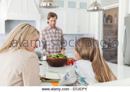 Mother helping daughter with homework while father prepares food at kitchen island - Stock Photo