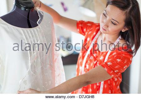 Female seamstress working in home studio - Stock Photo