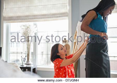 Female seamstress doing alterations in home studio - Stock Photo