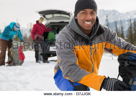 Portrait of man with friends preparing for winter hike in mountains - Stock Photo