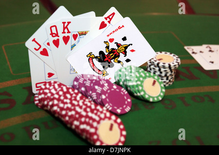 green casino table with chips and a hand of a royal flush in a poker game and a joker in the pack - Stock Photo
