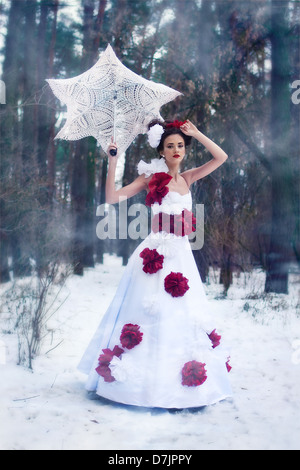 Pretty girl is walking in the snow with an umbrella - Stock Photo
