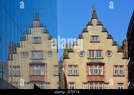 Old building and its reflection on modern glass cladding to new office block - Stock Photo