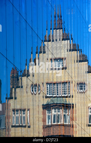 Reflection of old building in modern glass cladding to new office block - Stock Photo
