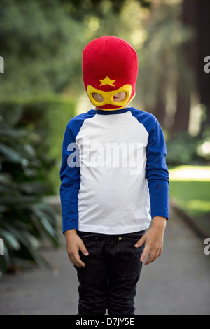 little boy wearing red and yellow superhero mask posing outside on the sidewalk, obscuring his eyes - Stock Photo