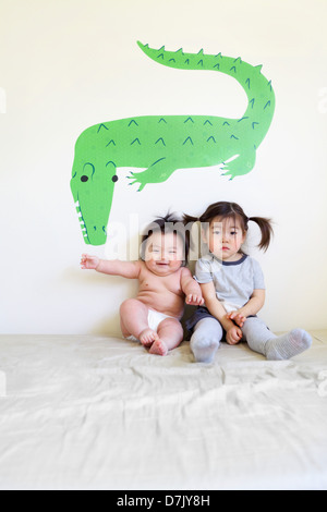 Two cute Korean American kids sitting on bed posing for camera in front of crocodile wall art - Stock Photo
