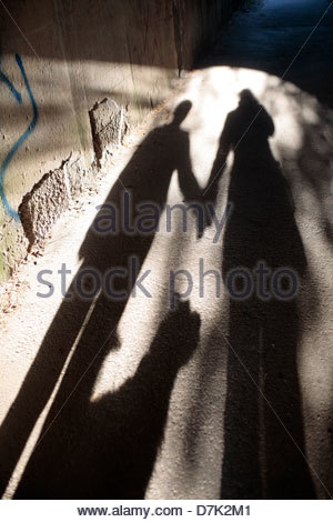 High angle view of shadow of a couple with a dog on the walkway - Stock Photo