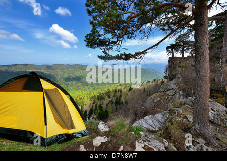 Russia. Lagonaki plateau. Adygea. Mountains in early spring, yellow camping tent on a shore in a morning light - Stock Photo