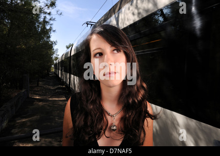 Close-up portrait of a young woman waiting for the train - Stock Photo