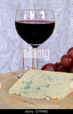 Wedge of blue French blue veined cheese with red wine and red grapes. - Stock Photo