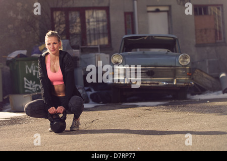 Resting fitness woman on the street having a break after exercising - Stock Photo