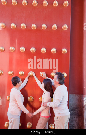 Granddaughter with grandparents standing next to the traditional red doors and holding hands - Stock Photo
