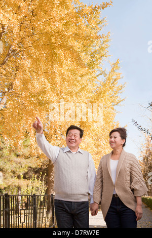 Mature Couple Walking Together in the Park - Stock Photo