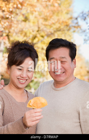 Mature Couple Looking at the Leaf in the Park - Stock Photo