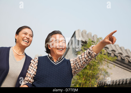 Happy senior couple outdoors pointing by traditional building in Beijing - Stockfoto