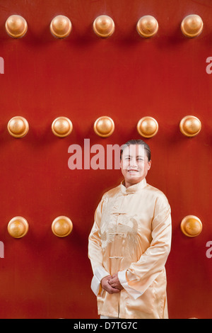 Mature woman in traditional clothes standing next to traditional Chinese door - Stock Photo
