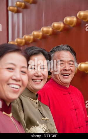 Group of mature people in traditional clothes standing next to traditional Chinese door, portrait - Stock Photo