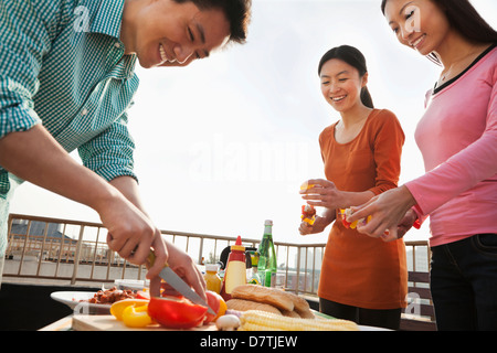 Group of Friend Preparing for a Barbecue on a Rooftop - Stockfoto