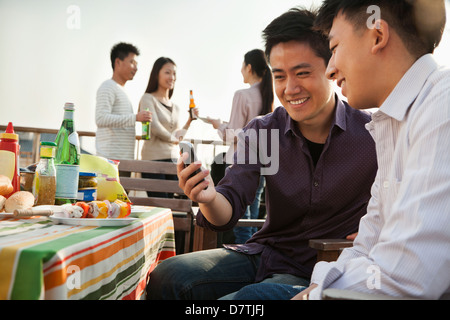 Friends Using Cell Phone at Rooftop Barbecue - Stock Photo
