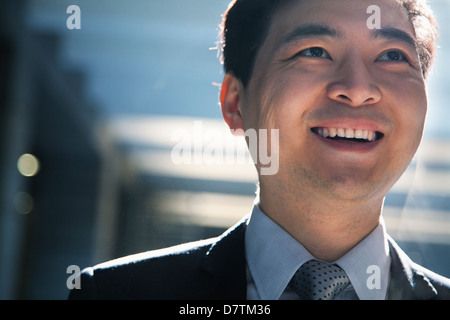 Portrait of smiling businessman in a parking garage - Stock Photo
