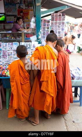 Three novice monks buying comics in the town market, Kengtung (Kyaingtong), Shan State, Burma - Stock Photo