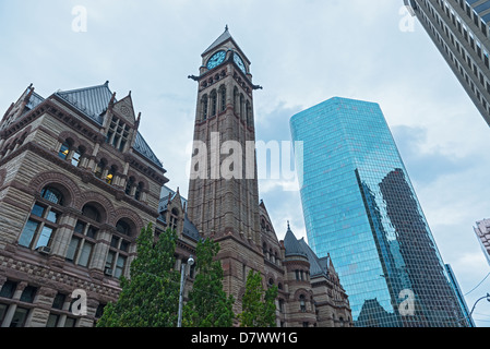 A view of the Old City Hall in Toronto with modern office buildings around it under blue skies. - Stock Photo