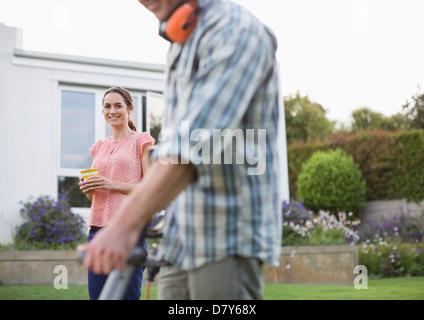Woman watching man work in garden - Stock Photo