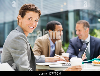Businesswoman smiling in meeting outdoors - Stock Photo
