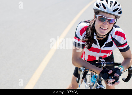 Cyclist smiling on rural road - Stock Photo