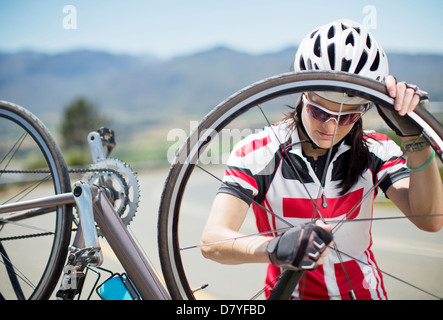 Cyclist adjusting tire on rural road - Stock Photo