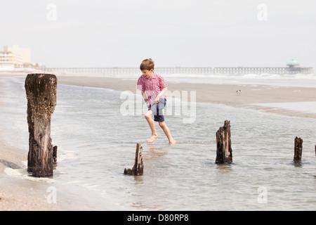boy walking through tide - Stock Photo
