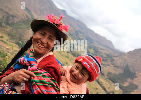 Quechua lady in traditional dress, carrying her son on her back. Cuzco, Peru - Stockfoto