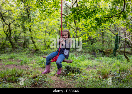 3 year old girl happily playing outdoors on a swing in woodland. - Stock Photo