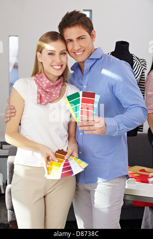 Young happy couple standing with color samples fan in studio - Stock Photo