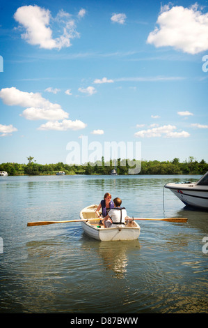 Two young people take a rowing boat out on the Norfolk Broads during a hot summers day - Stock Photo