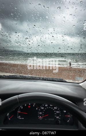 UK south coast beach through a car windscreen on a rainy day in Spring/Summer with a man running - Stock Photo