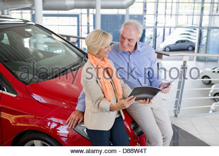 Couple looking at brochure and leaning on automobile hood in car dealership showroom - Stock Photo