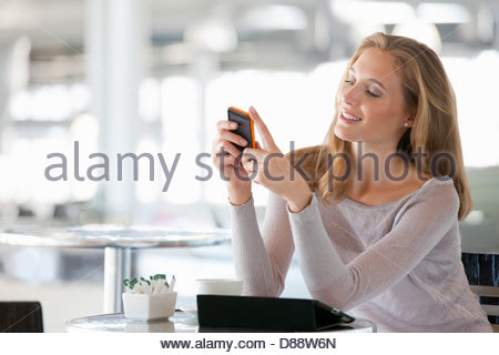Woman checking cell phone at cafe table - Stock Photo