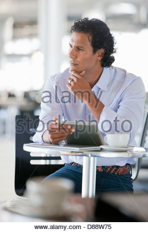 Pensive man with digital tablet at cafe table - Stock Photo
