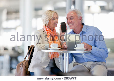 Smiling couple talking on cell phone and using digital tablet at cafe table - Stock Photo