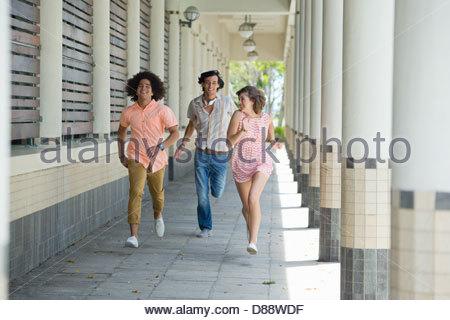 Smiling friends running along corridor - Stock Photo