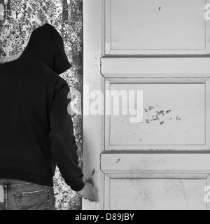 Hooded figure exiting through the door of an abandoned house. - Stockfoto